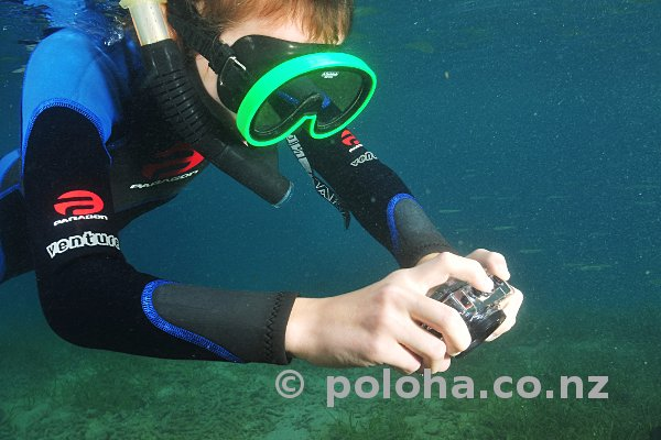Young snorkel diver with compact camera